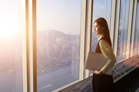 asian architect: Successful female office worker with net-book is standing in skyscraper interior against big window with city view on background. Proud asian woman architect looking satisfied with completed project