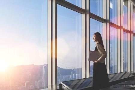 Erfolgreiche weibliche Büroangestellte mit einem Netto-Buch auf den Hintergrund in Wolkenkratzer Interieur gegen große Fenster mit Blick auf die Stadt steht. Stolze asiatische Frau Architekt Blick mit abgeschlossenes Projekt zufrieden
