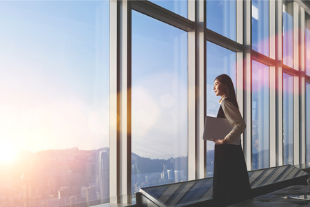 modern lifestyle: Successful female office worker with net-book is standing in skyscraper interior against big window with city view on background. Proud asian woman architect looking satisfied with completed project