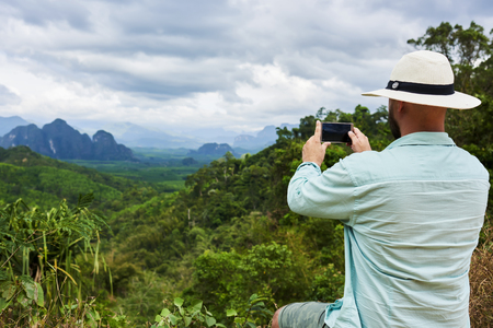subtropical: Back view of a man wanderer is shooting video on smart phone, while is sitting on a mountain against subtropical forest. Young hipster guy is taking photo on cell telephone of a beautiful jungle view