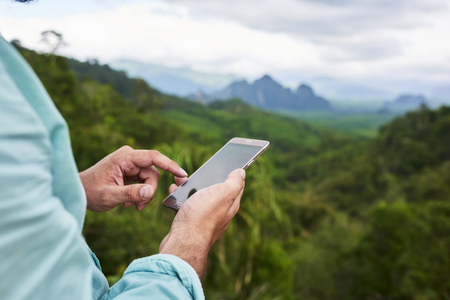 Closeup of a man's hand is holding mobile phone with copy space screen against blurred jungle landscape. Young male is searching information on cell telephone during summer adventure in Thailand