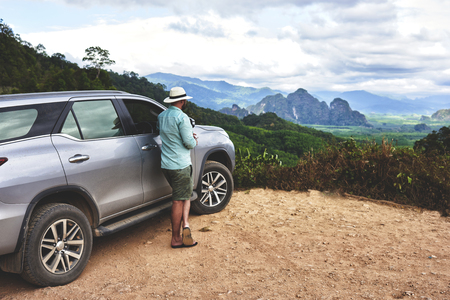 Back view of a young man wanderer is enjoying amazing jungle view, while is standing near his luxury suv car. Male traveler is looking away on the beautiful Asian landscape and high mountain