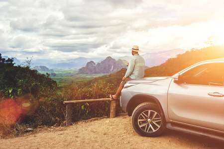 admiring: Dreaming man traveler is enjoying freedom and fantastic jungle view, while is sitting on a car hood in summer evening. Young male tourist is admiring amazing landscape, during road trip on cuv in Asia Stock Photo