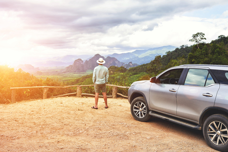 fantastic view: Back view of a man tourist is admiring fantastic view of a wild nature during summer weekend on car in Asia. Young male wanderer is enjoying fantastic jungle landscape, while is standing near his suv