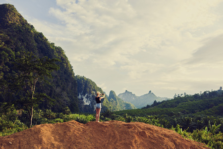 taking video: Back view of a woman is shooting video on cell telephone during summer vacation with daughter in Latin America. Female is taking photo with smart phone camera, while is standing against jungle scenery Stock Photo