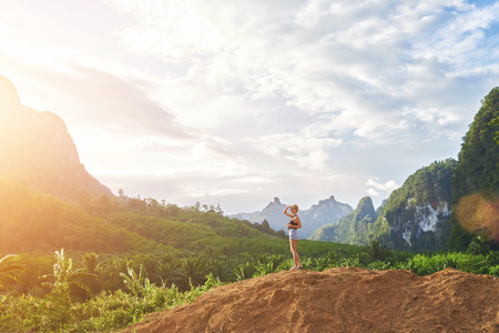 woman freedom: Hipster girl with cell telephone in hand is enjoying amazing jungle view during her summer adventures overseas. Young woman traveler is admiring wonderful landscape during her vacation in Thailand