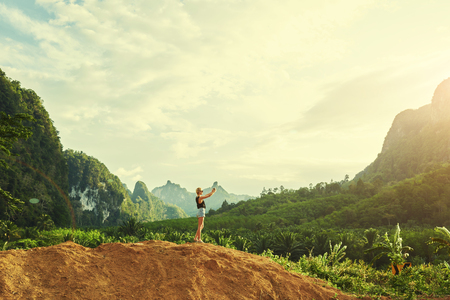 unforgettable: Hipster girl wanderlust is taking photo with mobile phone camera during unforgettable travel in Thailand. Young female is shooting video on cell telephone, while is standing against Amazon scenery Stock Photo