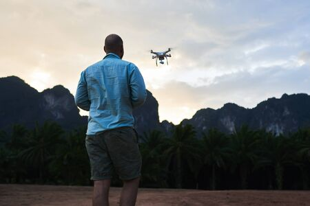 Back view of man wanderer is shooting video with radio controlled drone, agaist silhouette of rock mountains at sunset. Male blog author is taking photos on flying multicopter during trip in Asia