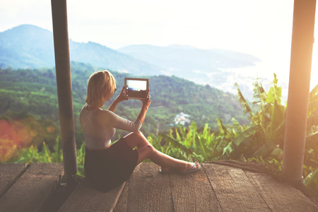 jungle green: Female traveler is shooting video on portable touch of a wonderful Amazon view during her unforgettable summer weekend. Young woman tourist is taking photo with digital tablet camera of jungle view