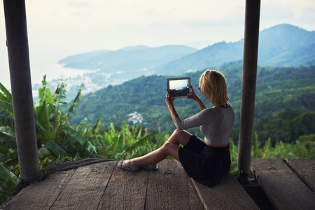 woman mountain: Back view of a young woman wanderer is making photo with portable touch pad camera during her vacations in Thailand. Female tourist is shooting video on digital tablet of a beautiful jungle landscape Stock Photo