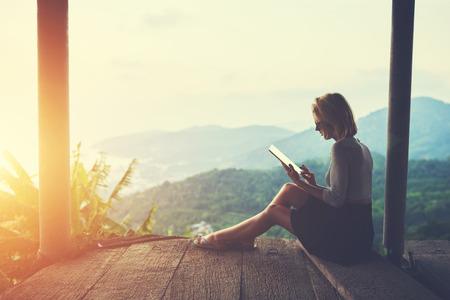 Femme est de taper quelque chose dans le journal sur le pavé tactile, tout est assis contre le paysage asiatique étonnant dans la belle soirée d'été. Femme regarde la vidéo sur tablette numérique lors de son voyage en Thaïlande