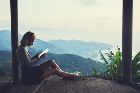 unforgettable: Young female freelancer is working in network via touch pad, while is sitting against beautiful view background with copy space for your advertising text message during her unforgettable trip in Asia