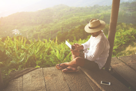 electronic book: Man traveler is reading electronic book on portable touch pad, while is relaxing in the fresh air during trip in Asia.Male freelancer is working on digital tablet, while is sitting against jungle view Stock Photo