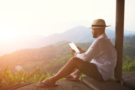 book page: Young man traveler is holding digital tablet with empty screen background with copy space for your advertising content. Male tourist is using touch pad, while is sitting against amazing jungle scenery