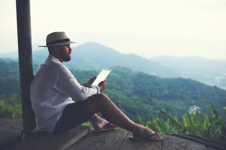 admiring: Man wanderer enjoying amazing jungle landscape and holding in hands portable touch pad with copy space on the screen. Young male explorer is using digital tablet while admiring wild mountains nature