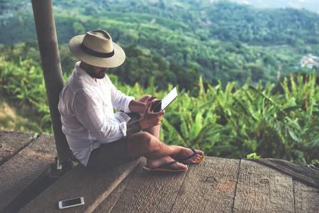 Man utas digitális tabletta, míg ül szemben szép ázsiai táj nyáron útra. Férfi vándor tartja touch pad, míg pihentető szabadban útja során Thaiföldön