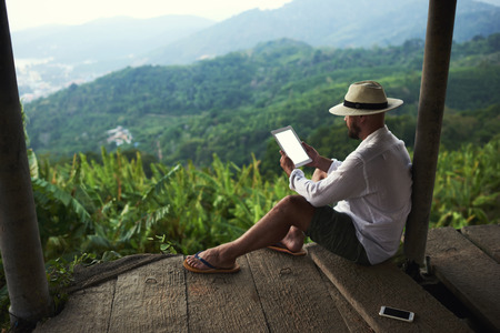 Male wanderer is holding portable touch pad with copy space on the screen for your text message or promotional content.Young man is reading financial news on digital tablet during his trip in Thailand