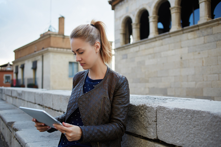 electronic pad: Charming woman student is reading electronic book on touch pad during break between lectures in university. Female tourist is searching in internet via digital tablet information about history of city Stock Photo
