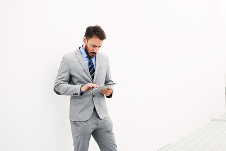 economist: Man successful economist is searching in internet via touch pad needed for conference information, while is standing in office interior near copy space for your advertising text message or content Stock Photo