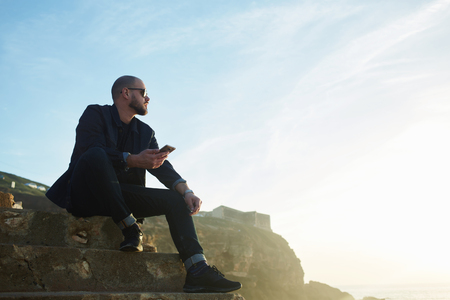 high speed internet: Handsome man in sunglasses is using High Speed Internet on mobile phone, while rest in the fresh air against blue sky with copy space.Stylish hipster guy is holding cell telephone during recreation Stock Photo