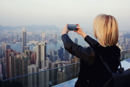 taking video: Woman wanderer is taking photo on mobile phone camera of big Hong Kong city, while is standing on a roof high building.Hipster girl is shooting video of the view on cell telephone during trip in China