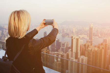 Young hipster girl with a rucksack on back is shooting video on mobile phone of an amazing view of Hong Kong. Blonde female traveler is making photo with cell telephone camera of China landscape Stock Photo