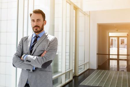 Homme d'affaires prospère habillé en costume coûteux est debout dans le couloir de son entreprise près copie espace pour votre message texte publicitaire ou gestionnaire mâle content.Young promotionnel est posant après briefing