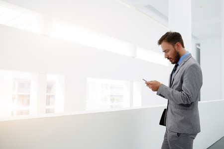 suppression: Worried businessman is reading e-mail on mobile phone from investor about suppression of the financing of his project, while is standing in office interior near copy space for your advertising content