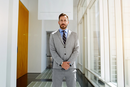 formal wear: Confident man owner of big successful company dressed in expensive classic suit is waiting for his business partners. Young male intelligent CEO in formal wear is standing in modern office interior Stock Photo