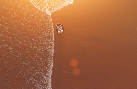 internet  broadband: Top view of air shooting from quadcopter of woman freelancer is using net-book for remote job, while is lying near sea on sun bed on beach with copy space. Internet access via mobile broadband modem Stock Photo