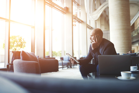 Serious man directeur général de grande entreprise prospère tient pavé tactile et appelant au gestionnaire d'entendre l'explication des raisons pour lesquelles le client a laissé un avis négatif sur le service sur le site officiel