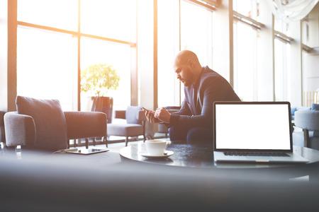 Man fiers CEO ordonne o-nline via voiture de téléphone cellulaire pour un voyage d'affaires, tout en est assis dans coworking café près de la table avec un ordinateur portable ouvert avec vide écran copie espace pour votre publicité Banque d'images