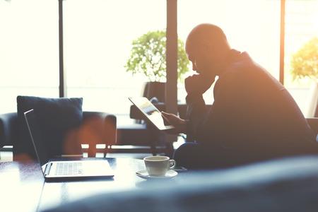 Sziluettje egy férfi képzett ügyvezetője elemzi a társaság tevékenységeinek segítségével touch pad és nettó könyv. Átgondolt férfi közgazdász olvas híreket hálózaton keresztül, a digitális tábla
