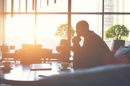 Silhouette du directeur de l'homme est de penser comment prévenir la crise de la société, tout en est assis avec net-book dans le café. financier Homme à regarder les nouvelles du monde sur ordinateur portable pendant la pause café Banque d'images - 59077043