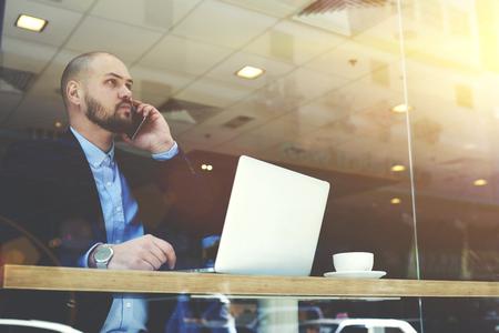 hombre barba: CEO joven barbudo de la gran empresa de éxito es tener una conversación con los clientes de telefonía móvil, mientras está sentado con el ordenador portátil portátil en un interior moderno restaurante durante la rotura de trabajo Foto de archivo