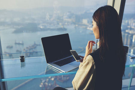 Young Asian businesswoman is holding mobile phone with blank display, while is sitting in skyscraper building at the table with open laptop computer with empty copy space screen for your advertising