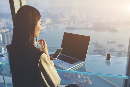 Woman owner of successful company is using mobile phone during webinar conversation in internet via net-book with staff during her business trip in Hong Kong, while is sitting in skyscraper building Banque d'images