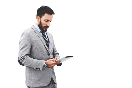 financier: Man skilled financier is reading financial news on web site via digital tablet, while is standing against clear wall background with copy space for your advertising text message or promotional content