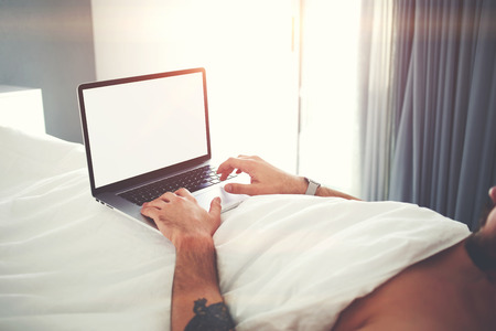 searching information: Closely of man successful freelancer is using laptop computer for remote job, while is relaxing in bed in home interior. Male is searching information on web site via net-book with copy space screen