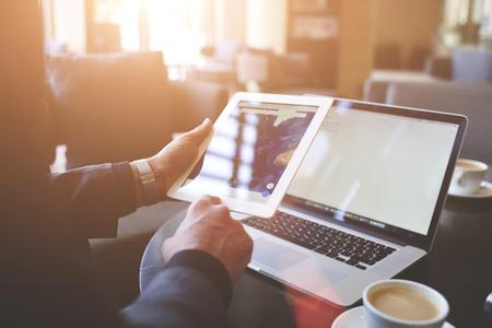 trader Homme cherche des informations sur les pages Web via tablette numérique portable. Gros plan du pavé tactile dans la main man`s et ordinateur portable avec copie espace sur les écrans pour votre message texte publicitaire.