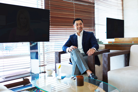 Cheerful Asian businessman in formal wear is smiling for someone, while is sitting in modern restaurant interior near two blank TV screens with copy space for your text message or promotional content