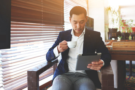 Fiatal magabiztos üzletember kezében csésze kávét, és figyeli a világ hírei internettel hordozható touch pad. Szakképzett férfi vezérigazgató olvas pénzügyi információkat a digitális tábla nyugalmi kávézó