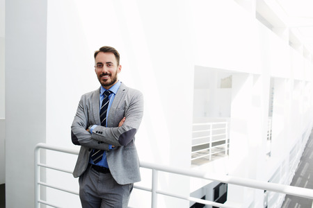Sourire travailleur homme du gouvernement habillé en costume de luxe est debout dans un intérieur moderne pendant la pause de travail à proximité de l'espace de copie pour votre publicité message texte ou le contenu. CEO mâle heureux regarde la caméra