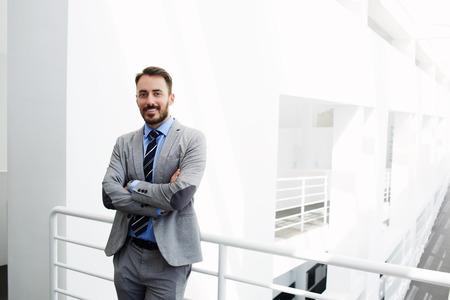 Uśmiechnięty pracownik człowiek rząd ubrany w luksusowym garniturze stoi w nowoczesnym wnętrzu w czasie przerwy w pracy niedaleko miejsca kopiowania dla wiadomości tekstowej lub treści reklamowych. Szczęśliwy mężczyzna CEO patrzy na aparat fotograficzny