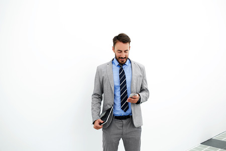 brokerage: Young man successful employee of brokerage firm with portable touch pad in hand is reading good news from his client, while is standing near copy space for your advertising text message or content