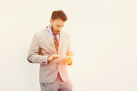 searching information: Young successful businessman or experienced leadership is searching information on web site via touch pad for meeting with employees,while is standing near copy space for your advertise text message Stock Photo
