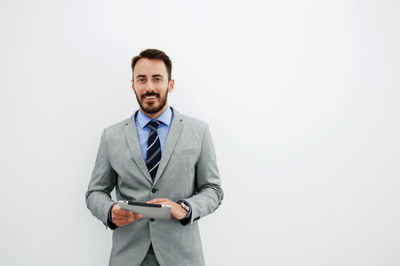 Smiling man managing director in luxury suit is holding portable digital tablet and looking at camera, while is standing in office against wall background with copy space for advertising text message Stock Photo