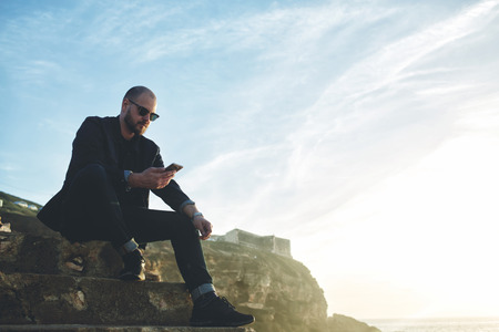 searching information: Young rich man dressed in trendy clothes and fashionable sunglasses is searching information in internet via mobile phone, while is sitting on rock cliff against sky with copy space for advertising Stock Photo