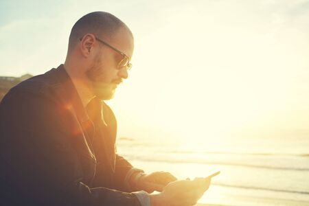 searching information: Young stylish hipster guy is searching information on web page on mobile phone,while relaxing during his spring weekend on the beach near sea with copy space background for your advertise text message Stock Photo
