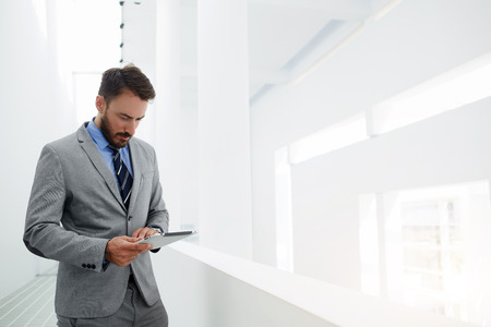 Man banker is searching information in the financial market via digital tablet, while is standing in hallway company near copy space. Serious male CEO is reading resume specialists before interview Zdjęcie Seryjne